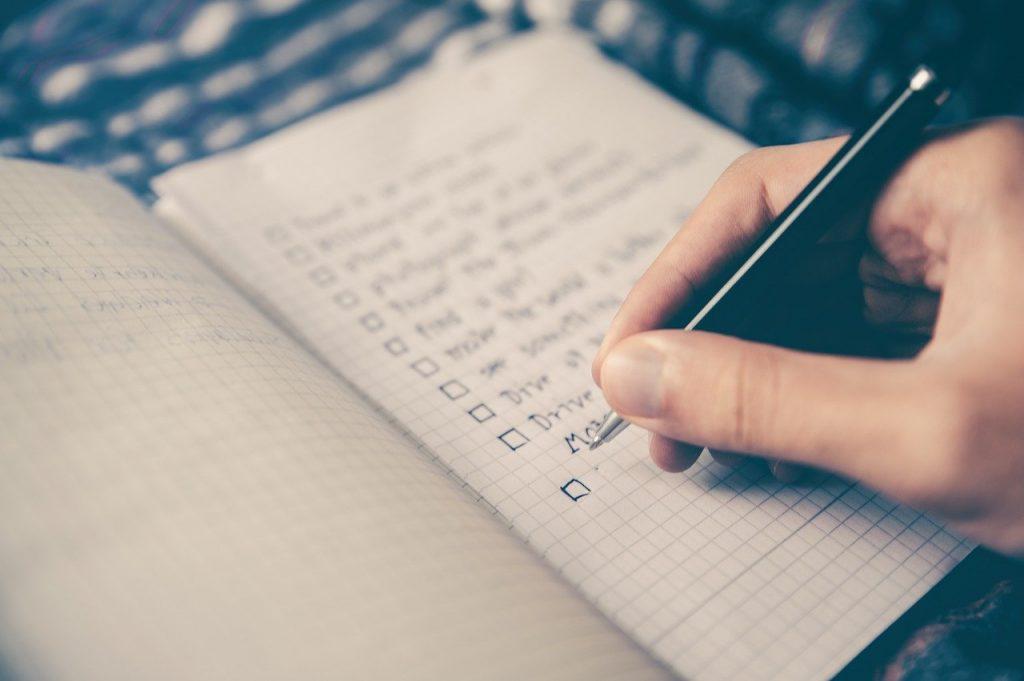 personne qui écrit une liste dans un carnet